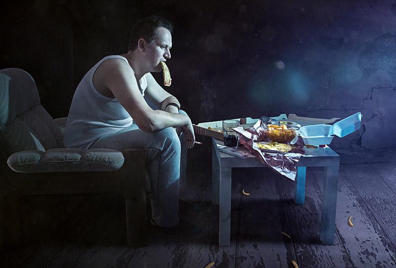 Imagen de un hombre cansado con malos hábitos de alimentación