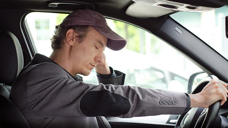 Hombre cansado conduciendo sin prestar atención por la falta de sueño