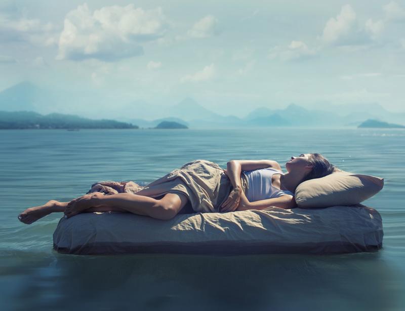 Chica en una cama flotando en un mar. Sensación de frescor