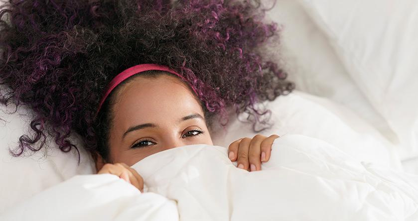 Mujer tumbada en la cama tapándose la mitad de su cara y sonriendo